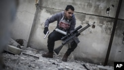 In this Friday, Jan. 18, 2013 photo, a sniper takes position on a roof during combat in the neighborhood of Saif Al-Dawlah in Aleppo, Syria.