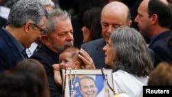 Mantan Presiden Brazil, Luiz Inacio Lula da Silva menggendong anak bayi mendiang Eduardo Campos dalam upacara pemakaman Campos di Recife (17/8).
