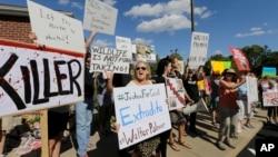 "Warga AS melakukan unjuk rasa di depan kantor dokter gigi Walter Palmer di Bloomington, Minnesota yang membunuh singa ""Cecil"" di Zimbabwe (29/7)."