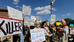 FILE: Protestors gather outside Dr. Walter James Palmer's dental office in Bloomington, Minn., Wednesday, July 29, 2015. Palmer reportedly paid $50,000 to track and kill Cecil, a black-maned lion, just outside Hwange National Park in Zimbabwe. (AP Photo/Ann Heisenfelt)