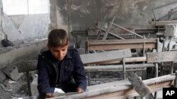 تصویر آرشیوی از یک کودک سوری در حال خواندن تکه کاغذی در داخل یک کلاس ویران شده در مدرسه ای در شهر حلب سوریه - آذر ۱۳۹۱