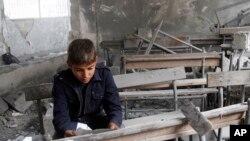 حلب کے ایک تباہ شدہ اسکول میں بیٹھا بچہ