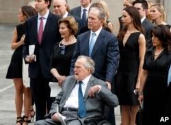 El expresidente George H.W. Bush, en silla de ruedas, su hijo el expresidente George W. Bush, y otros miembros de la familia observan mientras el ataúd de la exprimera dama Barbara Bush es colocado en un carro funeral luego de un servicio religioso en la iglesia episcopal St. Martin en Houston, Texas. Abril 21 de 2018.