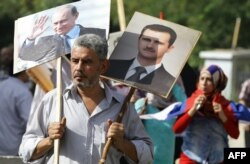 A Syrian man holds portraits of President Bashar al-Assad, right, and Russian President Valdimir Putin, left, as several hundred people gathered near the Russian Embassy in Damascus to express their support for Moscow's air war in Syria.