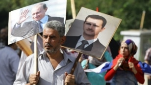A Syrian man holds portraits of Syrian and Russian leaders as several hundred people gathered near the Russian Embassy in Damascus to express their support for Moscow's air war in Syria, just before two rockets struck the compound, sparking panic, Oct. 13, 2015.