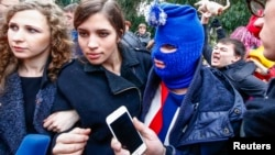 FILE - Russian punk band Pussy Riot members Maria Alyokhina (L) and Nadezhda Tolokonnikova (2nd L), along with a masked member of the group, speak to journalists during the 2014 Sochi Winter Olympics, in Adler, Feb. 20, 2014.