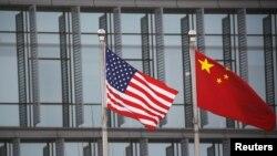 Bendera AS dan China berkibar di luar sebuah perusahaan Amerika di Beijing, China, 21 Januari 2021. (Foto: Reuters)