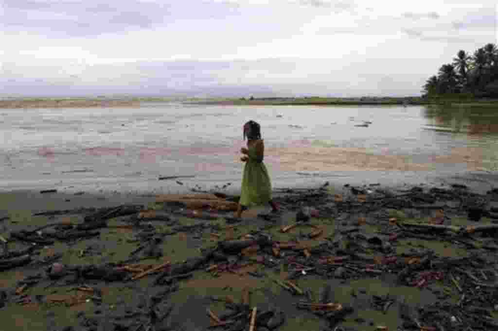 Una niña camina en una playa cubierta por escombros tras el paso del huracán Irene en Nagua, en la costa norte de la República Dominicana, 23 de agosto de 2011.