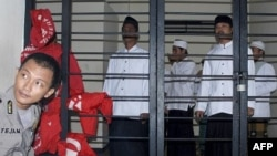 Indonesian Muslims who are on trial for their involvement in a fatal attack against followers of a minority Islamic sect earlier this year wait for the start of the hearing at a district court in Serang, Banten province, Indonesia, July 28, 2011