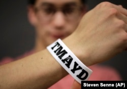 "Massachusetts Institute of Technology student Andy Trattner shows a wrist band that features the acronym TMAYD for ""Tell Me About Your Day,"" a campaign to encourage students to talk to one another."