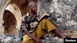 Un Tanzanien récite des versets du Coran assis parmi les ruines d'une ancienne mosquée sur l'île de Kilwa Kisiwani, Tanzanie le 30 octobre 2006.