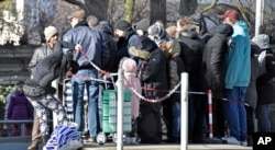 "People wait in front of the food bank ""Tafel"" for free food in Essen, Germany, Feb. 24, 2018. Essen's division of the charitable organization announced not to take any new migrant customers because their number rises up to 75 percent and would block out needy elderly German people."