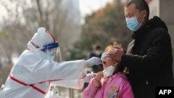 中國武漢的醫務人員在給一個女孩進行核酸檢測。(2020年3月5日)