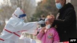 中国武汉的医务人员在给一个女孩进行核酸检测。(2020年3月5日)