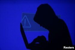 FILE - A hooded man holds a laptop computer as blue screen with an exclamation mark is projected on him in this illustration picture taken on May 13, 2017.