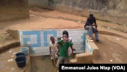 """Des enfants puisent de l'eau à une source au quartier """"Damas"""" à Yaoundé, au Cameroun, le 28 janvier 2017. (VOA/Emmanuel Jules Ntap)"""