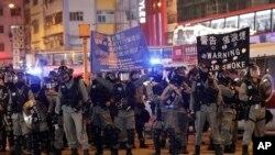 香港防暴警察在圣诞日向示威者展开警示将要采取镇压行动的旗子。(2019年12月25日)