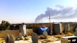 Asap hitam mengepul dari lokasi kilang minyak terbesar di Irak, Beiji, pasca serangan militan Sunni di wilayah itu (17/6).