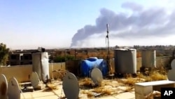 Una columna de humo se eleva de la refiner[ia de Beiji, al norte de Bagdad.
