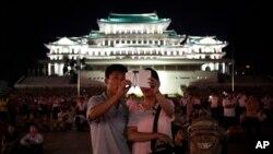 北韓一對夫婦在首都平壤金日成廣場利用智能手機拍攝煙花表現。(資料圖片)
