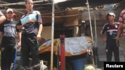 7月23日,一些路人站在八个月以南迪瓦尼耶省一个遭到炸弹攻击菜市场的汽车残骸和散落地面的青菜旁边