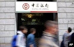 រូបឯកសារ៖ អ្នកធ្វើដំណើរដើរកាត់ផ្លាកសម្គាល់ធនាគារ Bank of China ស្ថិតក្នុងទីក្រុង Milan ប្រទេសអ៊ីតាលី កាលពីថ្ងៃទី១៥ ខែមេសា ឆ្នាំ២០១៥។