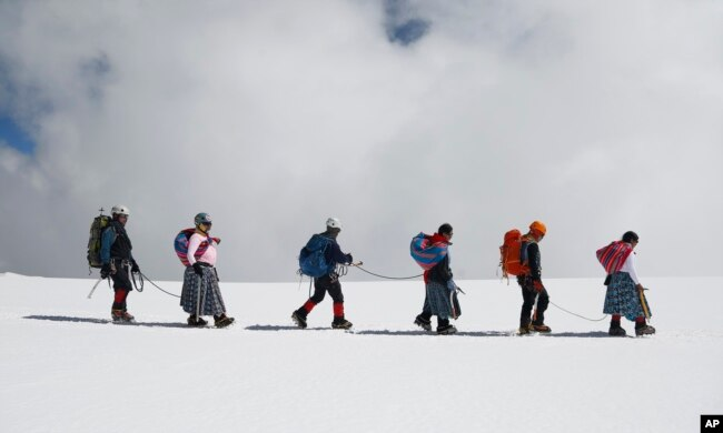 Para Cholita, menuruni gunung Huayna Potosi bersama suami mereka, yang bekerja sebagai pemandu profesional, di pinggiran El Alto, Bolivia, 17 Desember 2015. (AP)