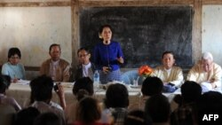 Myanmar opposition leader Aung San Suu Kyi (center) speaks to villagers near a Chinese-backed copper mine project, in Monywa northern Myanmar on March 13, 2013.