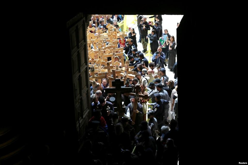 Православные верующие несут деревянные кресты в Храм Гроба Господня во время Крестного хода Страстной пятницы по Виа Долороса в Старом Городе Иерусалима.