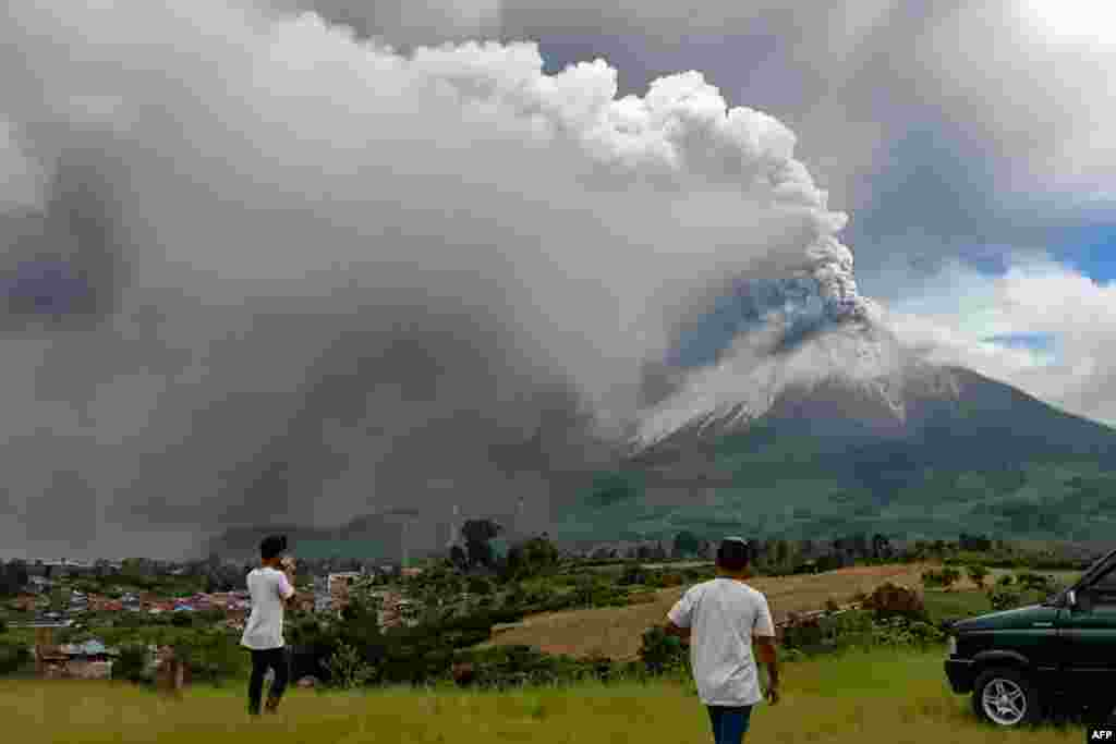 People look at Mount Sinabung spewing a massive column of smoke and ash as seen from Karo, North Sumatra, Indonesia.