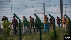 Migrants who successfully crossed the Eurotunnel terminal walk on the side of the railroad as they try to reach a shuttle to Great Britain, July 28, 2015 in Frethun, northern France.