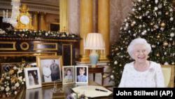En esta fotografía difundida el lunes 25 de diciembre de 2017, la reina Isabel II posa sentada en un escritorio en la habitación 1844 del Palacio de Buckingham, en Londres, después de grabar su mensaje por el día de la Navidad que sería transmitido a la mancomunidad británica.