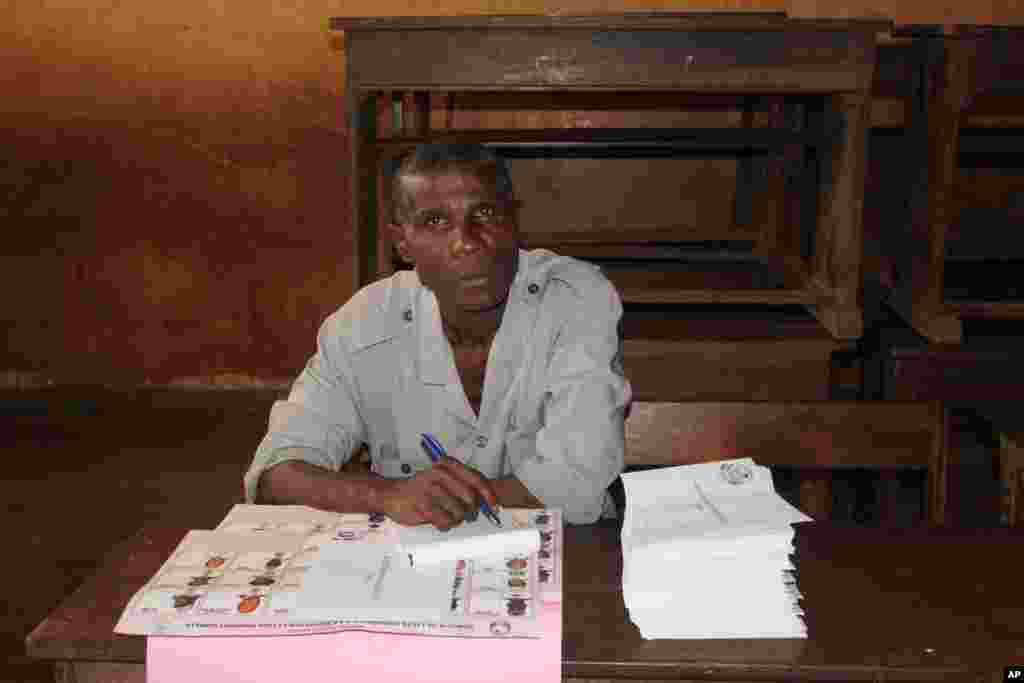 An election worker oversees the distribution of legislative election ballot papers at a polling station in Conakry, Guinea, Sept. 28, 2013.