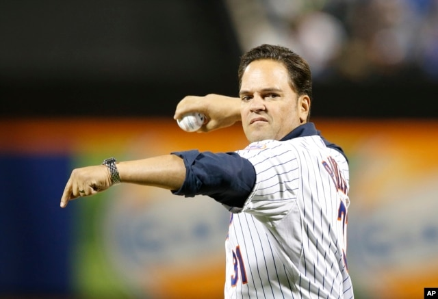 FILE - Retired New York Mets catcher Mike Piazza winds up before throwing out the ceremonial first pitch in a baseball game between the Mets and the New York Yankees in New York, Sept. 20, 2015.