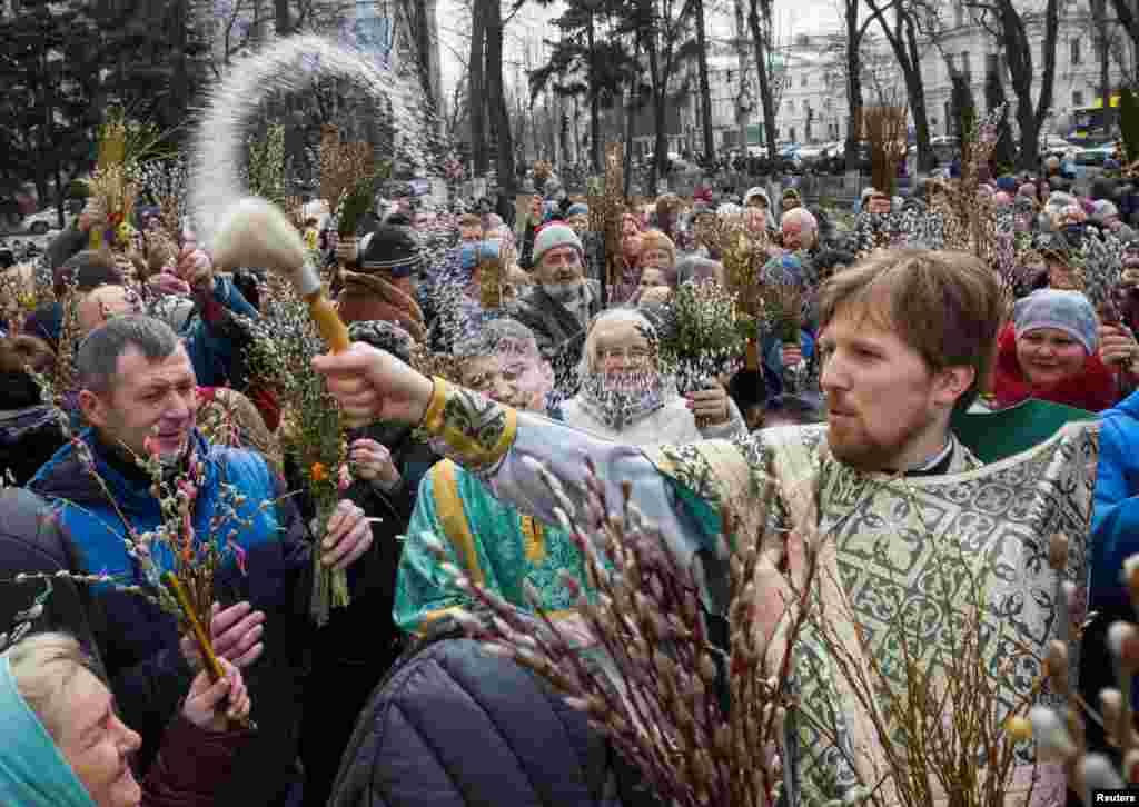 បព្វជិតម្នាក់បាចទឹកមន្ត ខណៈដែលអ្នកមានជំនឿជាច្រើនប្រារព្ធទិវា Palm Sunday នៅក្នុងក្រុង Kyiv ប្រទេសអ៊ុយក្រែន។