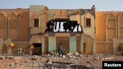A man walks past the destroyed former customs building, which was used as a base by radical Islamists, in Gao, Mali, February 28, 2013.