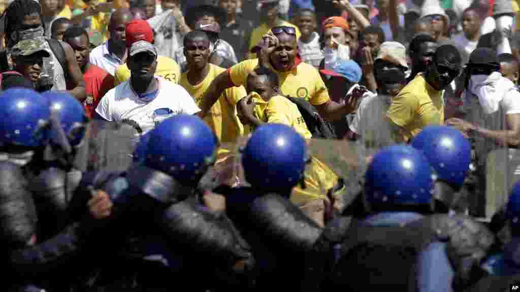 Les étudiants jettent des pierres contre des policiers ant-émeute à l'extérieur du bâtiment du syndicat à Pretoria, Afrique du Sud, 23 octobre 2015.(AP Photo/Themba Hadebe)