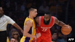 James Harden of the Houston Rockets (R) is guarded by Jeremy Lin #17 of the Los Angeles Lakers during the Lakers first regular season NBA game against the Houston Rockets, October 28, 2014 at Staples Center in Los Angeles, California. AFP PHOTO / Robyn B