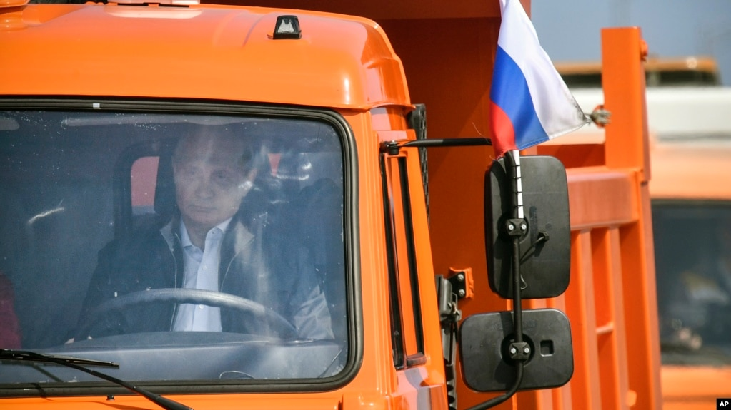 Russian President Vladimir Putin drives a truck to officially open the much-anticipated bridge linking Russia and the Crimean peninsula, during the opening ceremony near in Kerch, Crimea, Tuesday, May 15, 2018. (Alexander Nemenov/Pool Photo via AP)
