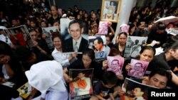 泰國民眾在等待泰王普密蓬遺體從醫院運回皇宮時舉起他的照片