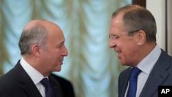 Menlu Rusia Sergei Lavrov (kanan) menyambut kedatangan Menlu Perancis Laurent Fabius sebelum berlangsungnya pertemuan terkait Suriah di Moskow (17/9).
