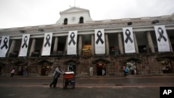 Black ribbon banners representing seven people who were killed by a dissident rebel group on the border of Ecuador with Colombia, hang outside the government palace in Quito, Ecuador, April 17, 2018.