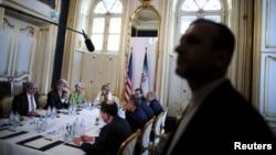 ເຈົ້າໜ້າທີ່ຮັກສາຄວາມປອດໄພ ອີຣ່ານ ຄົນນຶ່ງຢືນຍາມ ໃນ ຂະນະທີ່ລັດຖະມົນຕີຕ່າງປະເທດສະຫະລັດ ທ່ານ John Kerry (ທີສອງຈາກຂວາ) ພົບປະກັບບັນດາຜູ້ຕາງໜ້າອີຣ່ານ.