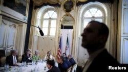 Un guardia cuida la seguridad mientars el secretario de Estado de EE.UU., John Kerry (segundo a la derecha) se reúne con la delegación iraní en Viena.
