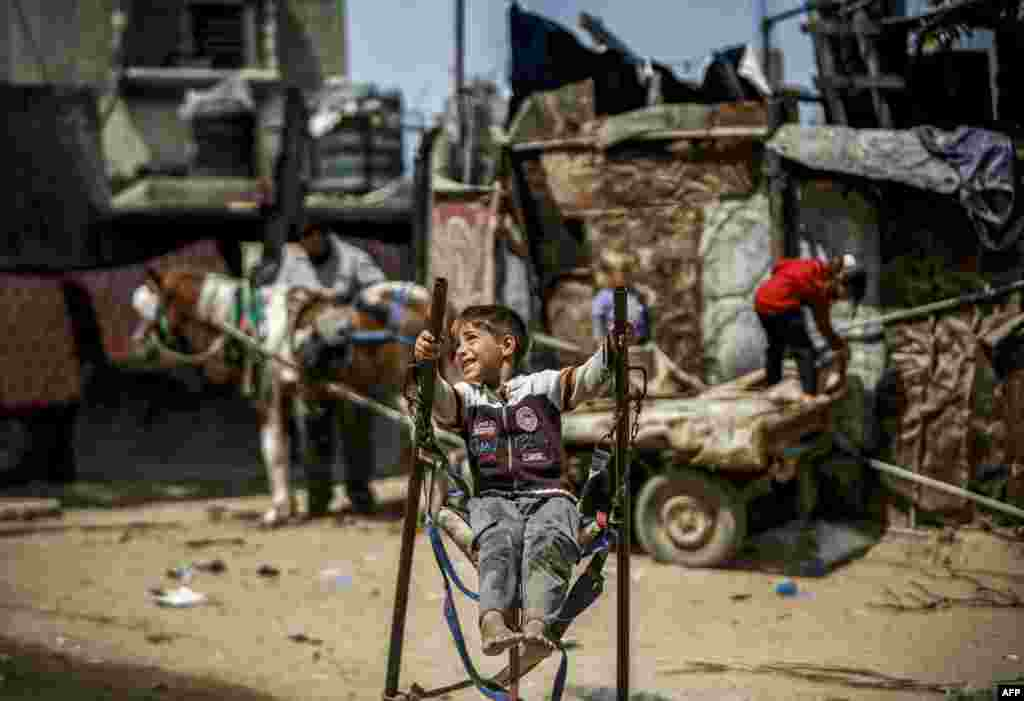 A Palestinian boy rides on a swing in a poor area of Beit Lahia in the northern Gaza Strip.
