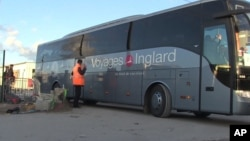 In this image taken from video, a bus carrying migrants leaves the migrant camp in Calais, France, Nov. 2, 2016.
