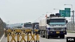 Truk-truk Korea Selatan mengangkut 300 ton terigu sebagai bantuan pangan untuk warga Korea Utara, sedang melewati perbatasan dua negara (26/7).