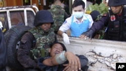 A Thai soldier injured in a fighting with Cambodia is helped by his comrades and a nurse after arriving at a hospital in Phnom Dongrak district of Surin province, northeastern Thailand, Friday, April 22, 2011. Thailand and Cambodia exchanged artillery and