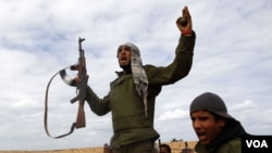 Tentara pemberontak meneriakkan 'Allahu Akbar' di tengah bentrokan dengan pasukan Gaddafi di jalan antara Ras Lanuf dan Bin Jawad, Senin (28/3).
