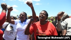 FILE: Zimbabwean war veterans who had gathered to demonstrate against a faction within the ruling Zanu PF party, reportedly led by the First Lady Grace Mugabe, vent their anger after they were dispersed by police using tear gas and water cannons in Harare, Thursday, Feb. 18, 2016. (AP Photo/Tsvangirayi Mukwazhi)